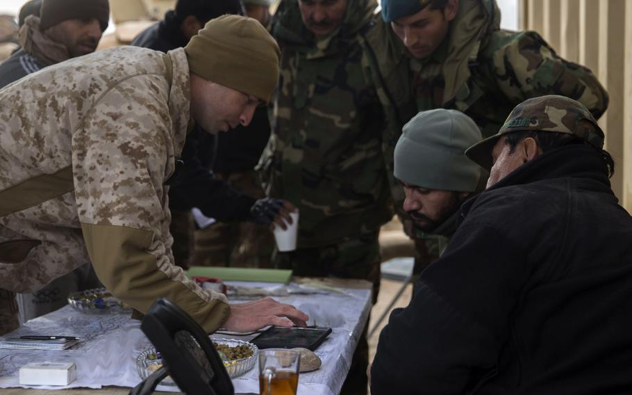 A U.S. Marine adviser with Task Force Southwest shows a possible enemy location to the Afghan tactical air coordinators during operation Maiwand 10 in Helmand province, Afghanistan, Dec. 26, 2017.