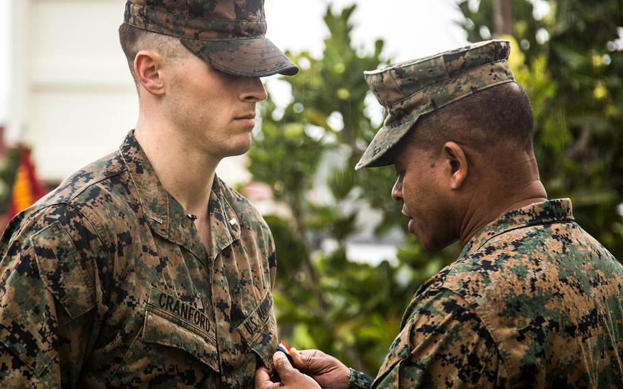 Marine 1st Lt. Aaron Cranford receives the Navy and Marine Corps Medal from Maj. Gen. Craig Timberlake, 3rd Marine Division commander, at Camp Schwab, Okinawa, Monday, Jan. 8, 2018.
