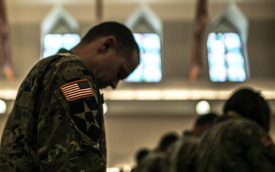 Soldiers bow their heads during a memorial service for Staff Sgt. Kyle LeFlore at Camp Humphreys, South Korea, Thursday, Jan. 11, 2018.