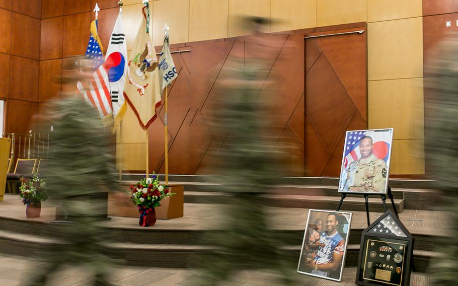 Soldiers walk by images of Staff Sgt. Kyle LeFlore at Camp Humphreys, South Korea, Thursday, Jan. 11, 2018.
