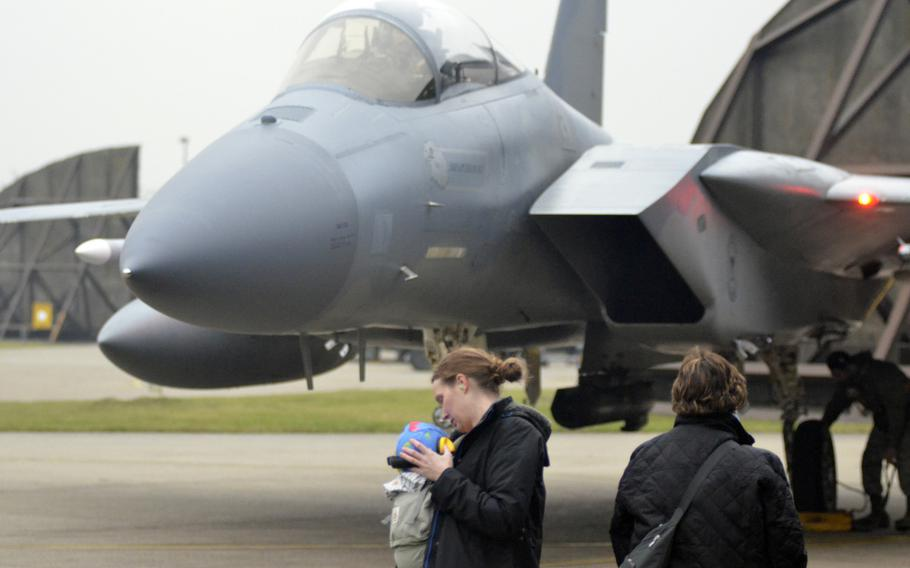"""Family wait for Capt. """"Nacho"""" Taylor to get out of an F-15C Eagle shortly after returning to RAF Lakenheath, England, from a NATO Baltic air-policing rotation at Siauliai Air Base in Lithuania, Tuesday, Jan. 9, 2018."""