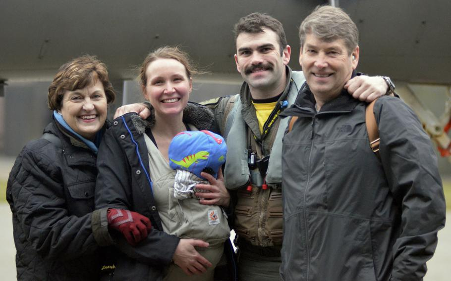 """Capt. """"Nacho"""" Taylor poses with his family after landing at RAF Lakenheath, England, from a deployment to Siauliai Air Base, Lithuania, Tuesday, Jan. 9, 2018."""