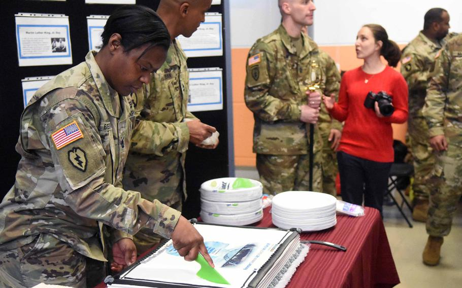 Equal opportunity adviser Sgt. 1st Class Altissa Butler cuts a cake at a ceremony in Vilseck, Germany, marking Martin Luther King's birthday, Thursday, Jan. 11, 2017.
