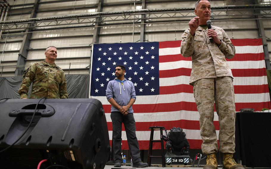 Command Sgt. Maj.John Wayne Troxell, senior enlisted adviser to the chairman of the Joint Chiefs of Staff, left, listens as Gen. Joseph Dunford speaks to troops at a Christmas Eve USO show at Bagram Air Field, Afghanistan, on Sunday, Dec. 24, 2017. At center is Medal of Honor recipient Capt. Flo Groberg.