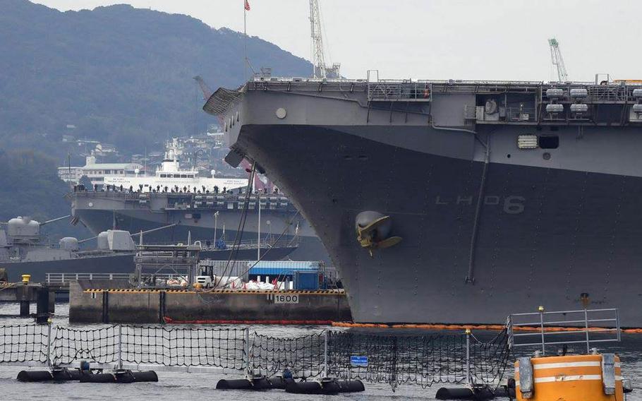 The amphibious-assault ship USS Wasp, background, pulls into Sasebo Naval Base, Japan, beside the USS Bonhomme Richard, Sunday, Jan. 14, 2018.