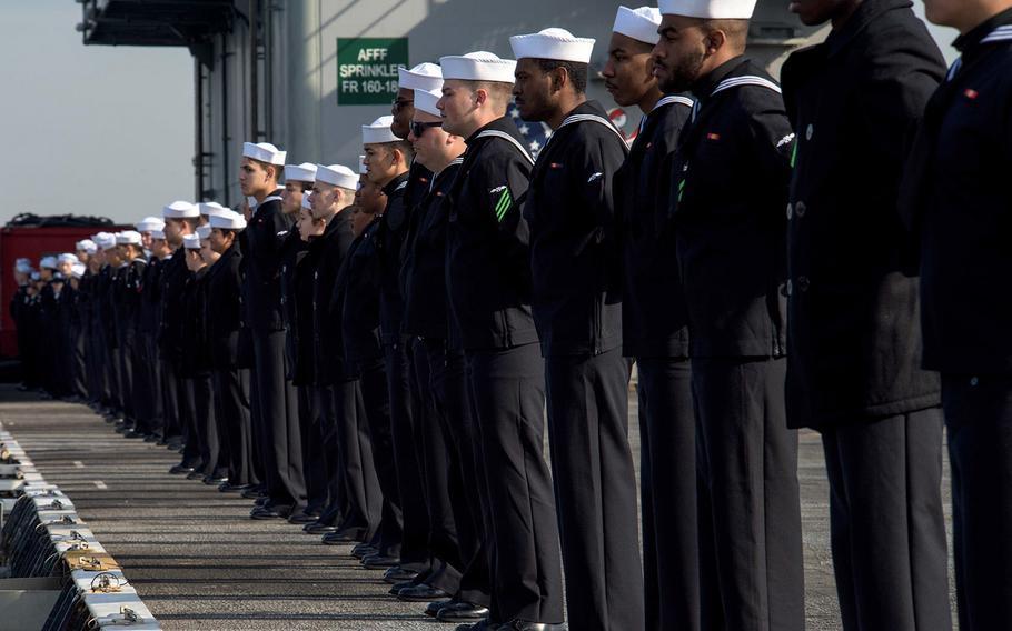 Sailors man the rails as the aircraft carrier USS Ronald Reagan arrives at Yokosuka Naval Base, Japan, Dec. 4, 2017.