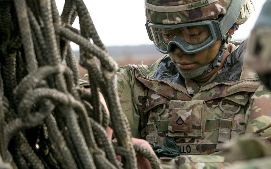 Pvt. Adrianne Castillo, automated logistics specialist with 299th Brigade Support Battalion, 2nd Brigade Combat Team, 1st Infantry Division, Fort Riley, Kan., inspects a rope harness while preparing equipment to be sling loaded from a helicopter at Skwierzyna, Poland, on Jan. 4, 2017.