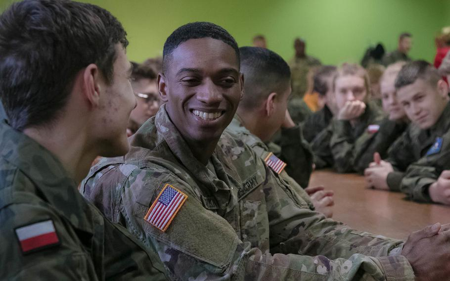 Sgt. Demetri R. Richardson, a wheeled vehicle mechanic from 2nd Armored Brigade Combat Team, 1st Infantry Division, Fort Riley, Kansas, answers questions about his life as an American Soldier from Polish high school cadets, Jan 15, 2018 at a school in Rzepin, Poland.
