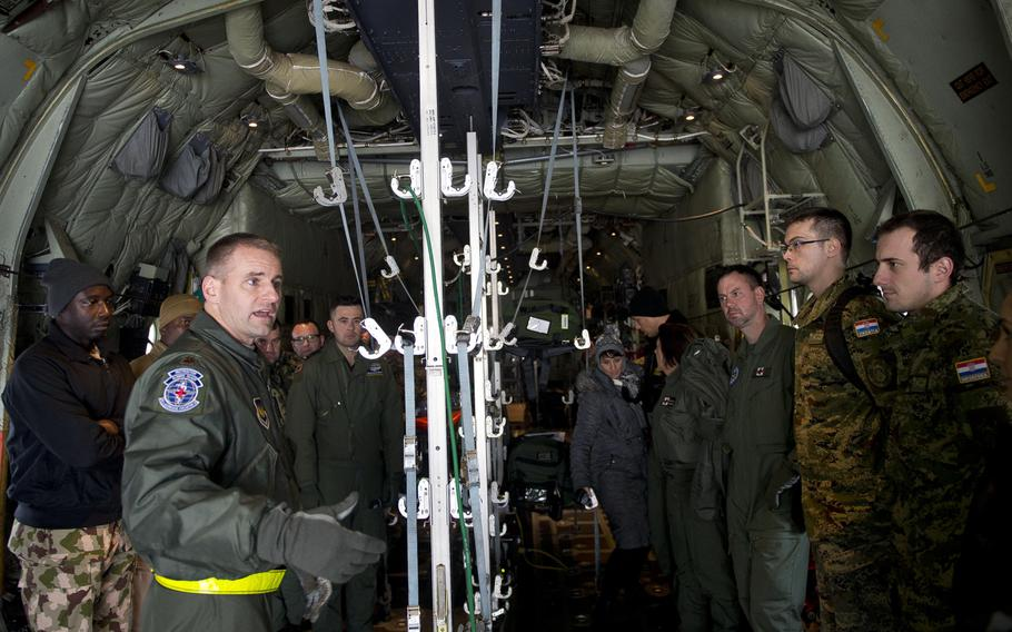 U.S. Air Force Maj. Jeremy Hicks, left, describes a training scenario to airmen from 13 countries during the African and European aeromedical evacuation symposium at Ramstein Air Base, Germany, on Thursday, Jan. 18, 2018.