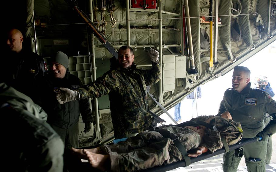 Albanian airmen load a simulated casualty onto a C-130J during a training scenario at Ramstein Air Base, Germany, on Thursday, Jan. 18, 2018.