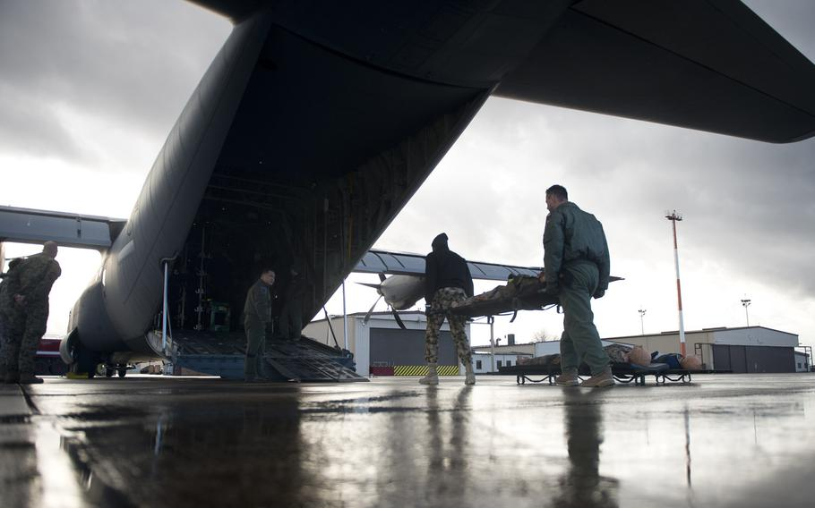 Slovenian Air Force 2nd Lt. Alvosa Lajbaher, right, and Nigerian Air Force Squadron Leader Benjamin Agom load a simulated patient onto a C-130J during aeromedical evacuation training at Ramstein Air Base, Germany, on Thursday, Jan. 18, 2018.