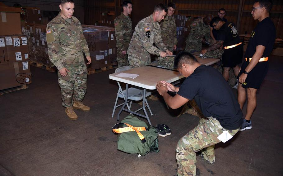 A soldier with the 25th Infantry Division in Hawaii tests the flexibility of the trousers of the Improved Hot Weather Combat Uniform earlier this month during fielding of about 800 prototypes of the lighter, faster-drying uniform.