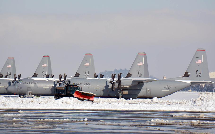 A snowplow passes C-130J Super Hercules aircraft at Yokota Air Base, Japan, Tuesday, Jan. 23, 2018.