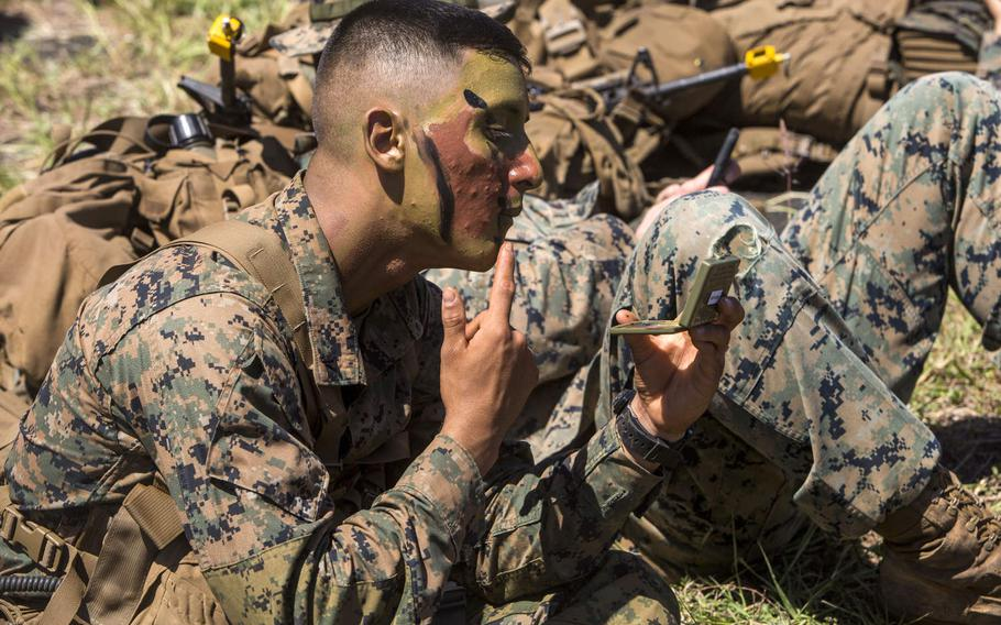 Lance Cpl. Isaac Lopez, an assaultman with 3rd Battalion, 3rd Marine Regiment, puts on camouflage paint during a Marine Corps Combat Readiness Evaluation at Marine Corps Air Station Kaneohe Bay, Oct. 3, 2017.