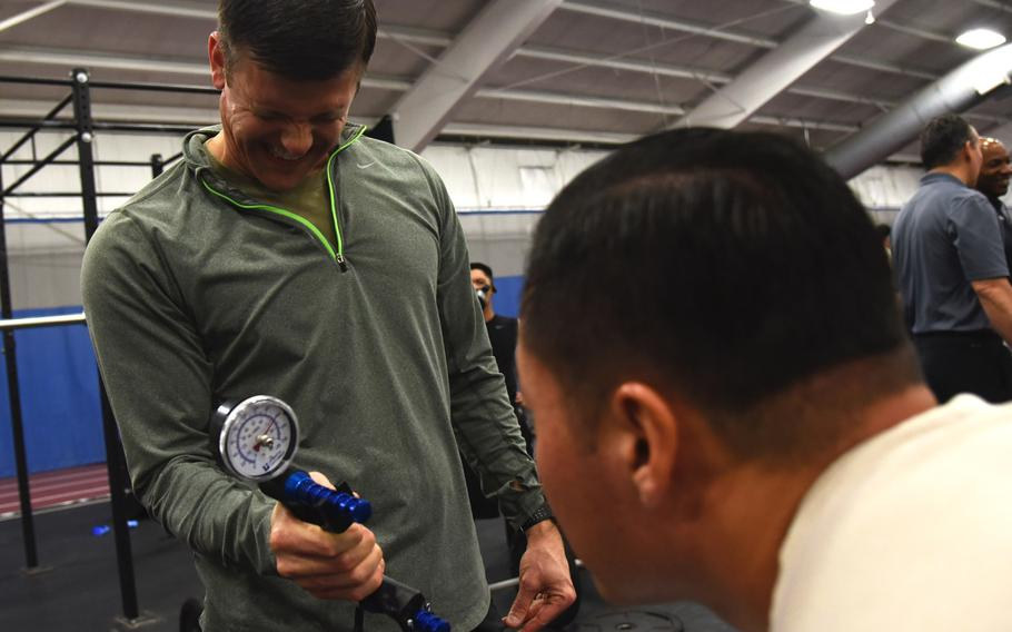 Master Sgt. Paul Foles, left, 17th Special Tactics Squadron, squeezes a dynamometer, which measures grip strength, during an occupational fitness demonstration at Joint Base Andrews, Md., Tuesday, Jan. 9, 2018.