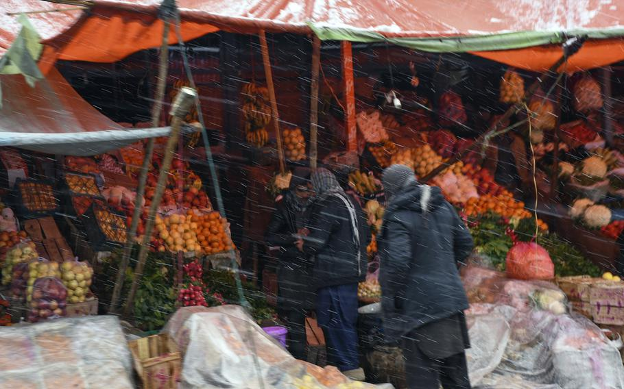Men in Kabul province, Afghanistan, shop for fruits and vegetables amid only the second winter snowfall in the country's capital and surrounding areas on Monday, Jan. 29, 2018.