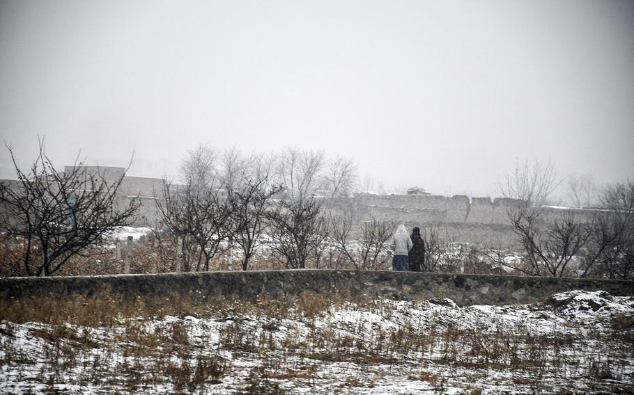 Two Afghans walk through a snowy field in Kabul province, Afghanistan, on Monday, Jan. 29, 2018.