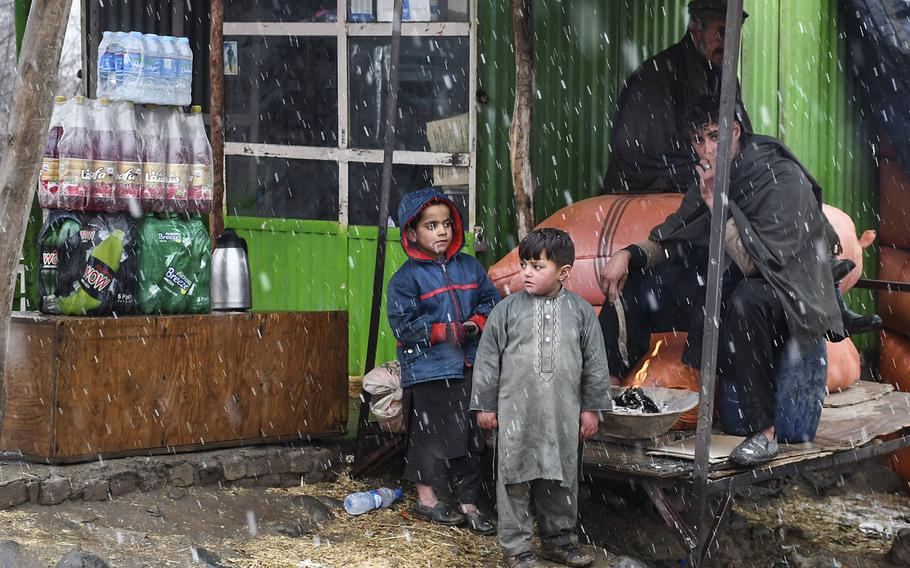 A group of Afghans huddle near a fire at a marketplace in Kabul province, Afghanistan, during a snow flurry on Monday, Jan. 29, 2018. The country has received little precipitation this winter, normally its wet season, which has concerned Afghans dependent on rain and snow for a bountiful crop.