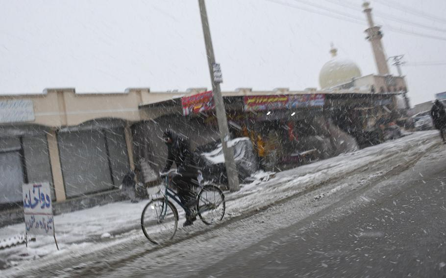 A man rides a big through a snow flurry on Monday, Jan. 29, 2018 in Kabul province, Afghanistan.