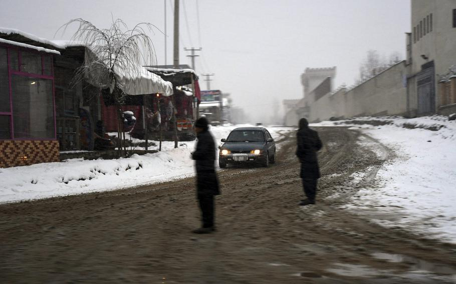 A car sloshes through the snow on Monday, Jan. 29, 2018 north of Kabul, Afghanistan.