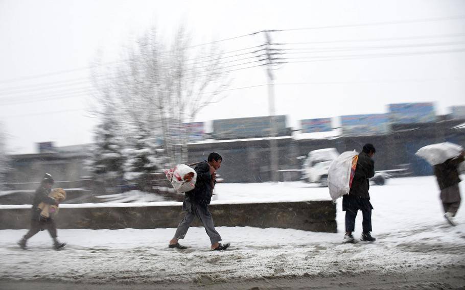People carry goods from the market north of Kabul on a snowy day in Afghanistan on Monday, Jan. 29, 2018.