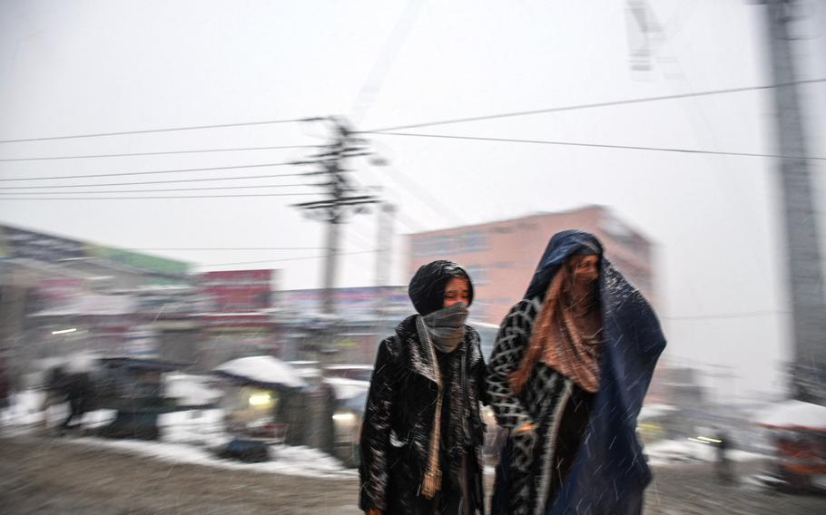 Two women, bundled up for the cold, cross a road in Kabul on Monday, Jan. 29, 2018. Snow blanketed the city for only the second time this winter after President Ashraf Ghani called on Muslims to pray for precipitation.