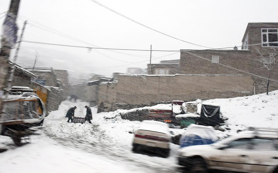 Two boys drag a carpet up a snowy hill on Monday, Jan. 29, 2018 in Kabul, Afghanistan.