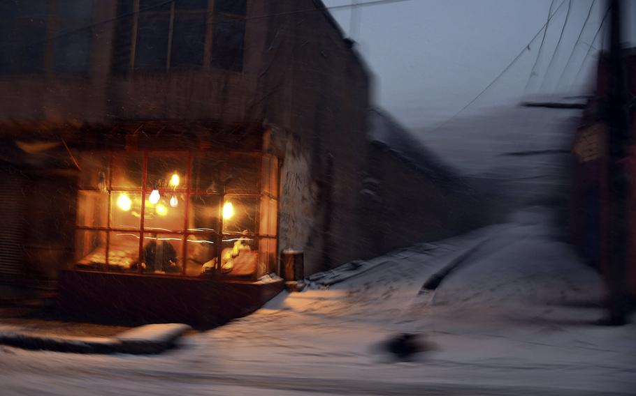 Light from a bakery fills the darkness on Monday, Jan. 29, 2018, one of the few snowy days in Kabul during the Afghan winter of 2017-2018.
