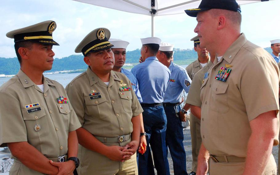 Former Navy Cmdr. Troy Amundson, right, is seen here speaking with members of the Philippine navy in Subic Bay in 2010.