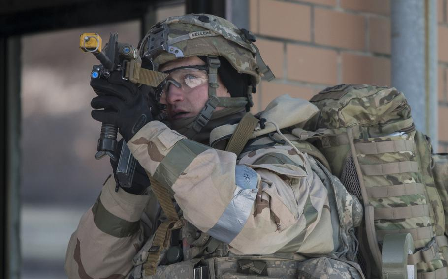 Sgt. Daviel Sellers, 1st Battalion, 9th Cavalry Regiment, 2nd Armored Brigade Combat Team, 1st Cavalry Division, scans for rooftop snipers before entering a building during a Warrior Strike drill last month.