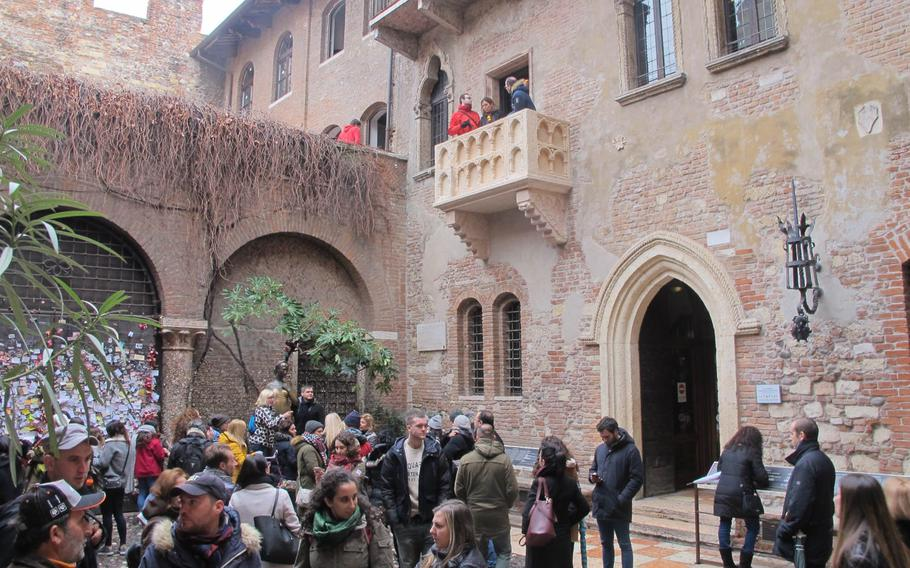"""A crowd in the courtyard of Juliet's house, complete with balcony added for ambience in Verona, Italy, where Shakespeare set """"Romeo and Juliet."""" Visitors cluster around Juliet's statue for photos. The house, one of the city's top tourist attractions, is less than an hour's drive from Vicenza."""