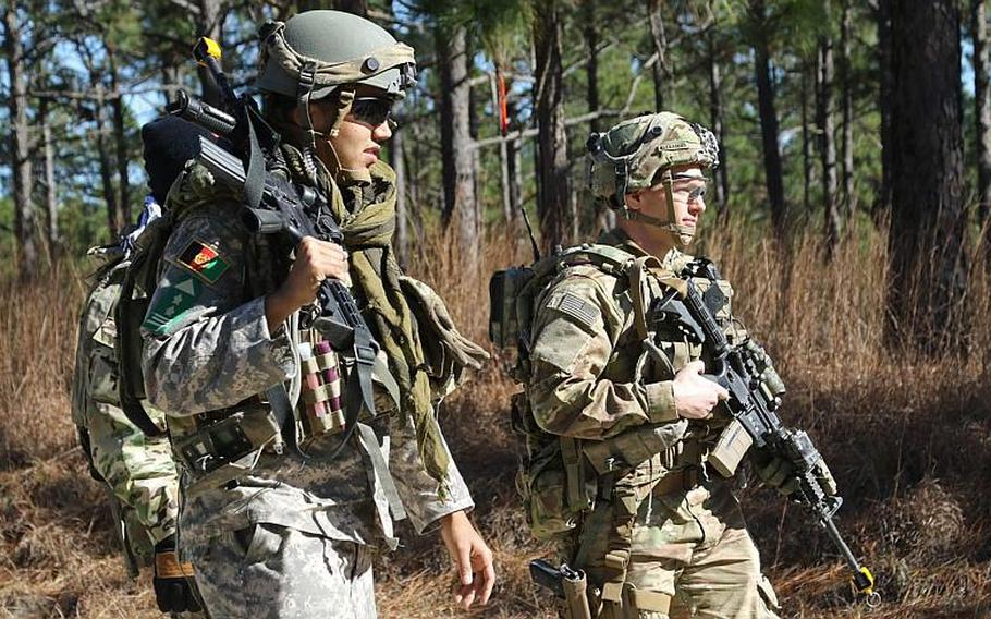 Capt. Justin M. Alexander, right, a combat advisor team leader for 1st Battalion, 1st Security Force Assistance Brigade, walks with an Afghan National Defense Security Forces role player during a simulated event at the Joint Readiness Training Center in Fort Polk, La., Jan. 13, 2018. The brigade has begun deploying to Afghanistan, according to the brigade Facebook page.