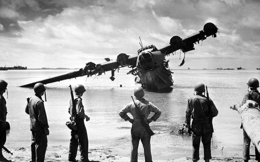 Soldiers examine a wrecked Japanese Kawanishi H8K near Makin, Gilbert Islands in November 1943. Two similar planes were used in a bombing raid on Oahu, Hawaii, on March 4, 1942.