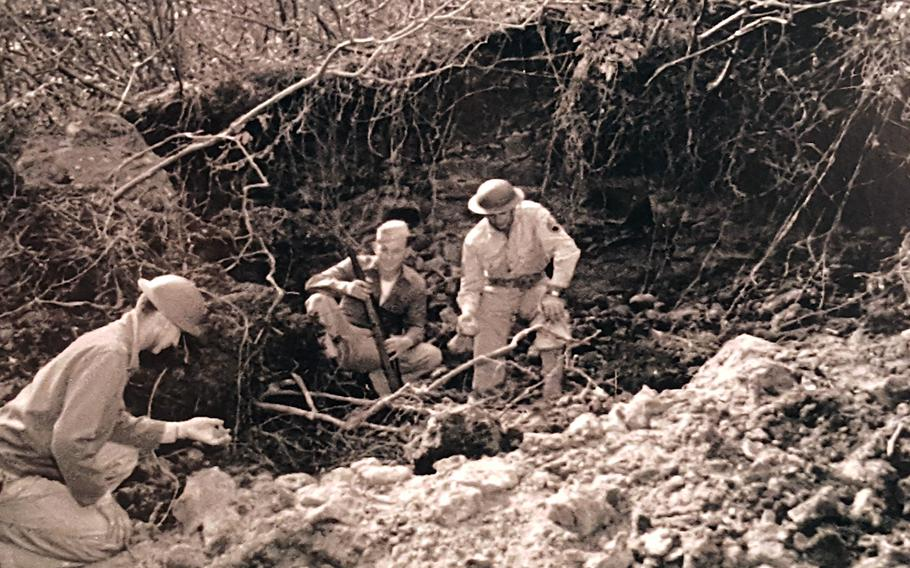 Soldiers inspect a crater left near Honolulu after a Japanese bombing raid on Hawaii, March 4, 1942, in this undated photo on display at the Pacific Aviation Museum in Honolulu.