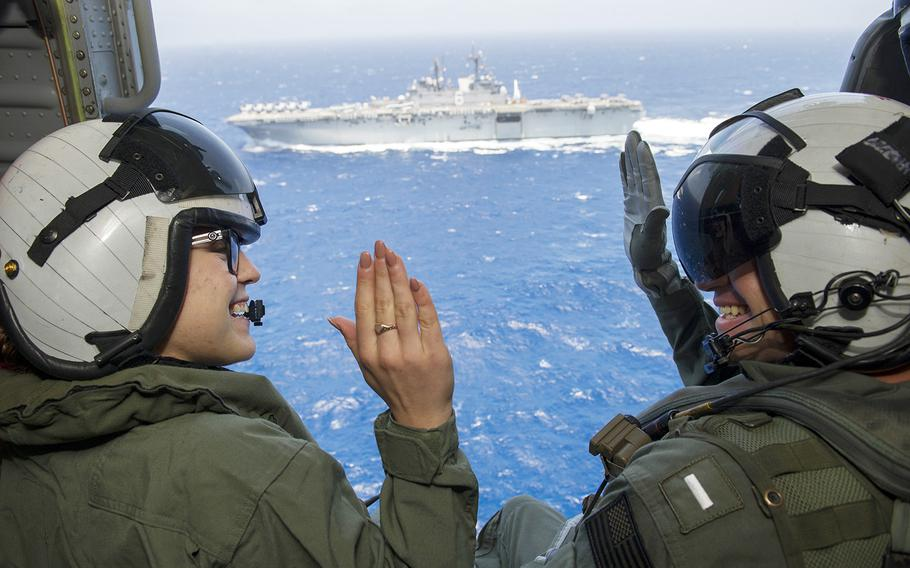 Petty Officer 3rd Class Sierra Rivera, left, of the amphibious assault ship USS America, repeats the oath of enlistment to Lt. j.g. Nicholas Haan aboard an MH-60 Sea Hawk helicopter.