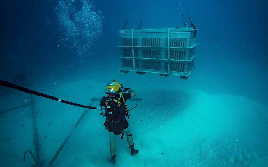 A Navy diver guides a salvage basket during an underwater recovery operation searching for World War II remains off the coast of Koror, Palau, Jan. 30, 2018.
