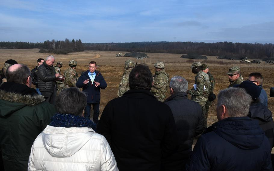 U.S. Army spokesman Andre Potzler speaks to a crowd of local, German mayors and community leaders while they watch artillery fire during exercise Dynamic Front, at Grafenwoehr, Germany, Monday, March 5, 2018.