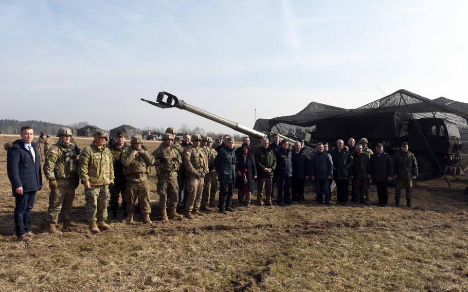 German mayors and community leaders and U.S. and German Army soldiers pose together during their visit on base to watch artillery fire during exercise Dynamic Front, at Grafenwoehr, Germany, Monday, March 5, 2018.