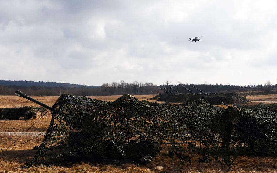 British artillery pieces prepare to fire as a U.S. Apache helicopter flies above during Exercise Dynamic Front 18 at Grafenwoehr, Germany on Wednesday, March 7, 2018.