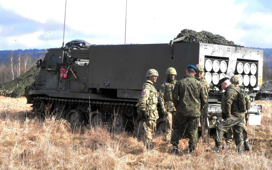 British and Polish soldiers talk by an M270 Multiple Rocket Launching System during Exercise Dynamic Front 18 at Grafenwoehr, Germany on Wednesday, March 7, 2018.