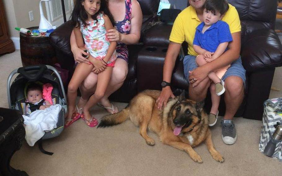 National Guardsman and former dog handler Julio Munoz, left, and his wife Shulammite, right with their children, and tactical explosives detection dog Ben during a visit to the home of Ben's adopted owner Kim Scarborough in August 2017. Scarborough sought to reunite the two after she adopted Ben from the Army in 2014