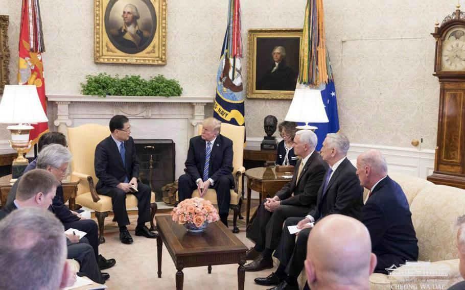 South Korean National Security Adviser Chung Eui-yong, left, speaks to President Donald Trump at the White House in the company of other U.S. and South Korean officials, Thursday, March 8, 2018.