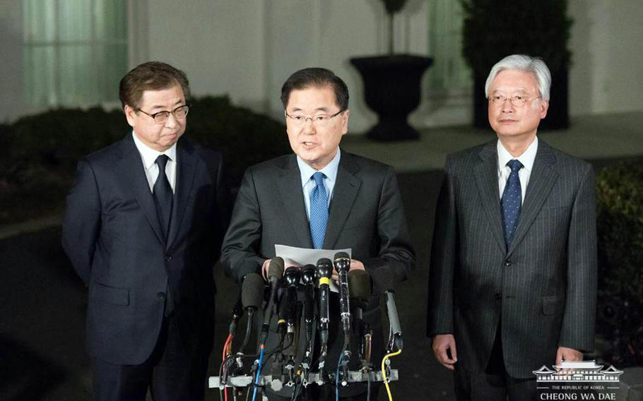 South Korean National Security Adviser Chung Eui-yong, flanked by National Intelligence Service chief Suh Hoon, left, and ambassador to the United States Cho Yoon-je, right, speaks to reporters outside the White House, Thursday, March 8, 2018.