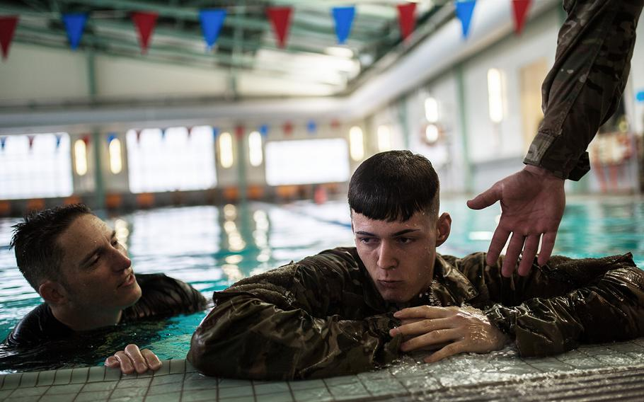 Michael Jagelski of 55th Military Police Company, 94th Military Police Battalion rests after finishing a water-survival event during a best-warrior competition at Camp Walker, South Korea, Monday, March 6, 2018.