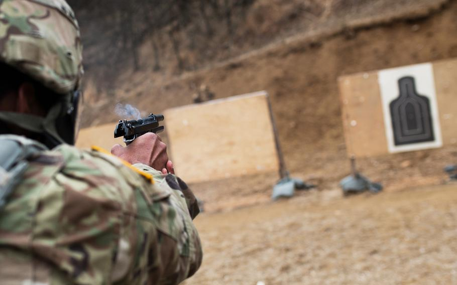 A 19th Expeditionary Sustainment Command best-warrior competitor fires his pistol during a stress shoot at Masan, South Korea, Wednesday, March 7, 2018.