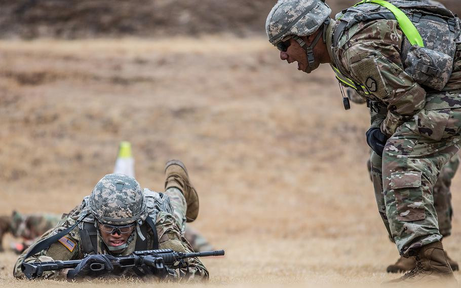 Pfc. Demarious Quick of Headquarters and Headquarters Company, 19th Expeditionary Sustainment Command receives extra encouragement during a stress shoot at Masan, South Korea, Wednesday, March 7, 2018.