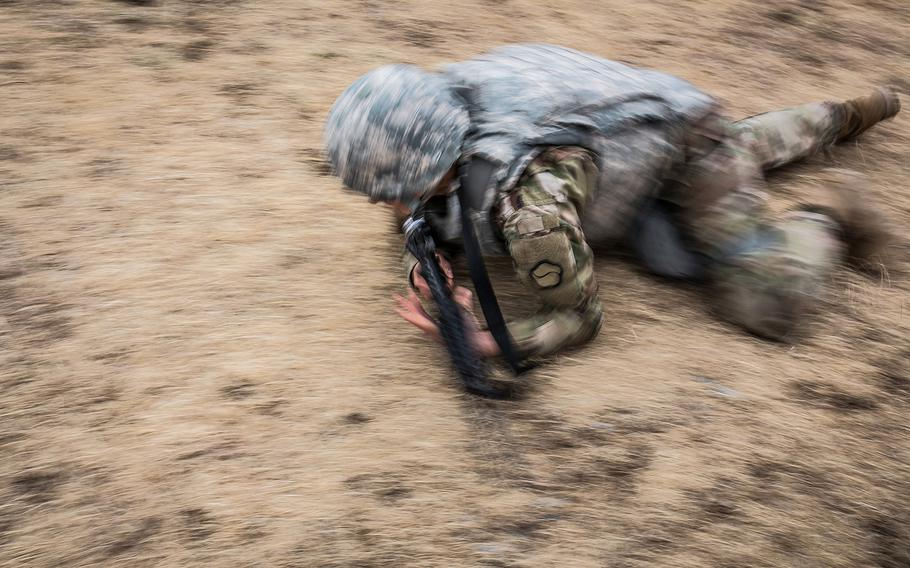 A 19th Expeditionary Sustainment Command best-warrior competitor low crawls during a stress shoot at Masan, South Korea, Wednesday, March 7, 2018.