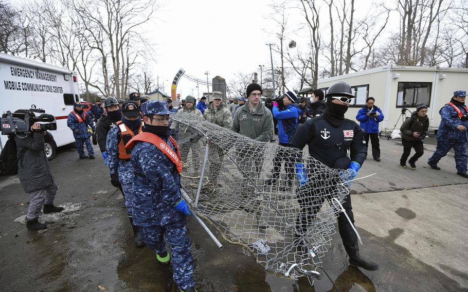 U.S. and Japanese servicemembers work together to clean up Lake Ogawara near Misawa Air Base, Japan, earlier this month after an F-16 jettisoned its fuel tanks because of an emergency.