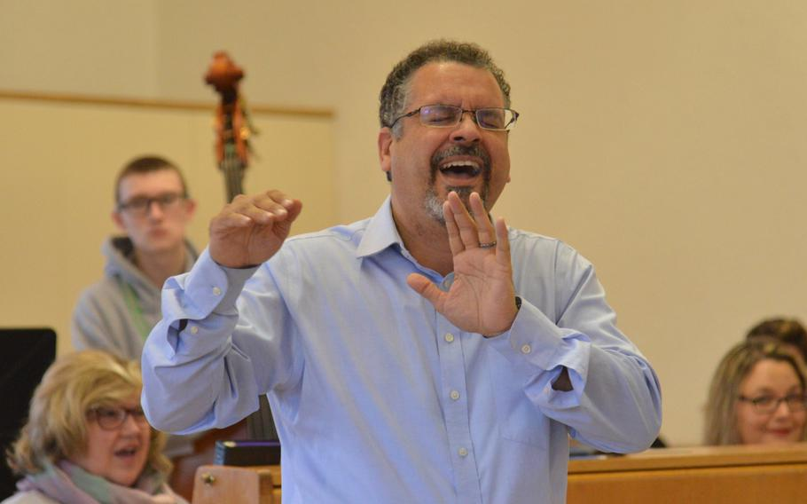 Jose Rivera, this year's guest conductor for the choir at the annual DODEA-Europe Honors Music Festival, describes to the choir what he wants to hear during a rehearsal, Tuesday, March 13, 2018.