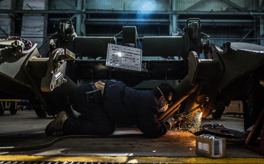 A worker at the Heavy Equipment Division welds a mine clearing claw at Camp Carroll, South Korea, Tuesday, March 6, 2018.